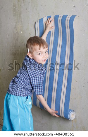 Boy with roll of wallpaper near wall. Flat repair