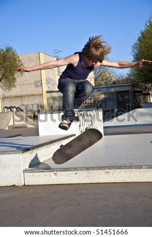boy with scateboard is going airborne at a skate park