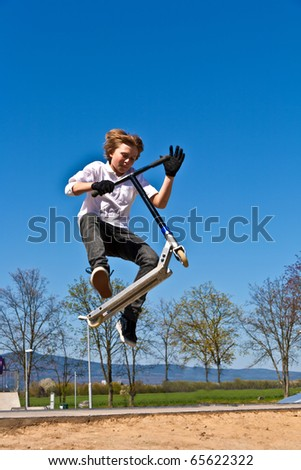 boy with scooter is going airborne at a skate park