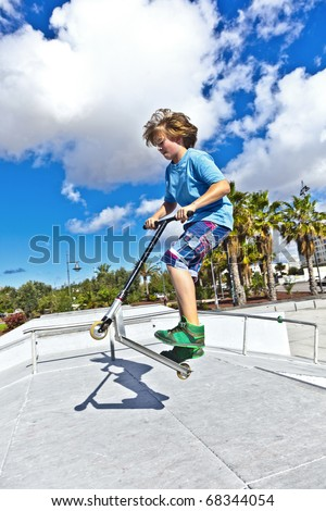 boy with scooter is jumping at the skate park