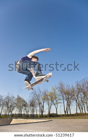boy with skate bard is going airborne at a skate park