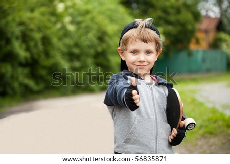 Boy with skateboard showing thumbs up sign outdoors