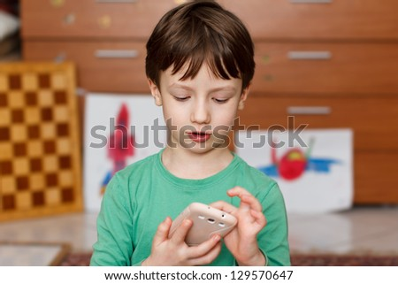 Boy with smartphone at home playing