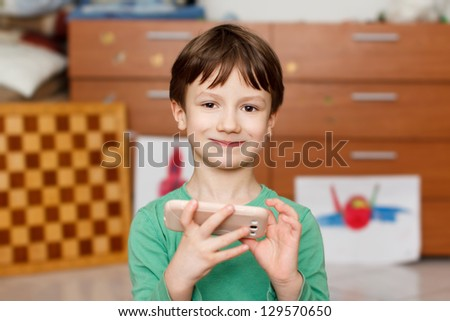 Boy with smartphone at home smiling - stock photo