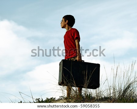Boy with suitcase on a dune
