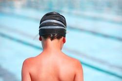 Boy with sunburn back in a swim cap by a pool.  Focus on shoulders