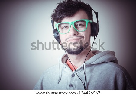 boy with sweatshirt and headphones on gray background