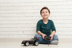 boy with toy car against a brick wall