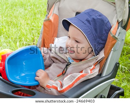 boy with toy in the stroller outside