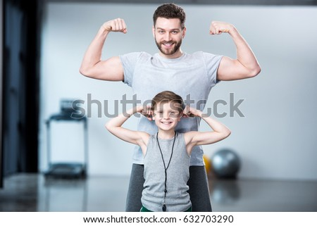 Boy with young man, his trainer or father showing muscles