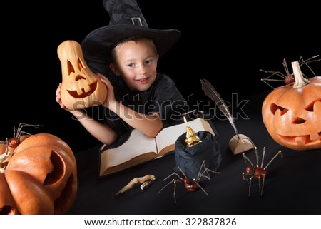 Boy wizard Halloween with pumpkins, magic book, spiders, dead man\'s fingers and candles, Isolated on black background
