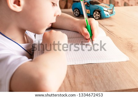 boy writes with a pen in a notebook with his left hand. left hand is more developed #1334672453