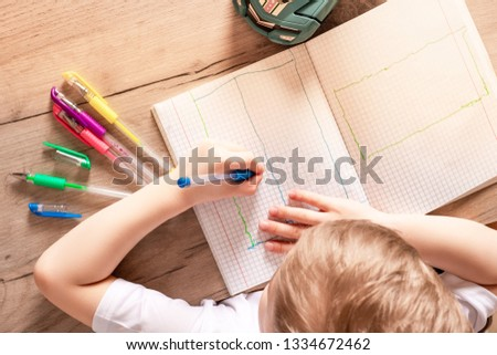 boy writes with a pen in a notebook with his left hand. left hand is more developed #1334672462