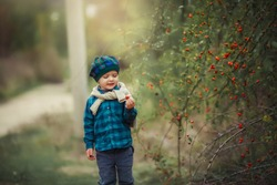Boy 5-7 years in the fresh nature in rubber boots and autumn clothes walking in the woods.