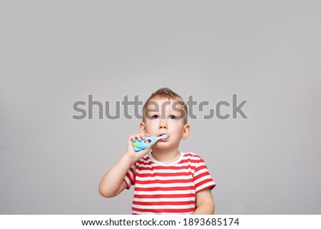 boy 2 years old brushes teeth with a toothbrush and looks up, gray background. prevention of child caries. oral hygiene in a child. copy space. Foto stock ©