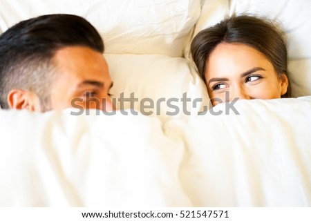 Boyfriend and girlfriend laying in a bed with white sheets - Young and beautiful couple happily looking at each other during bed time - Focus on the girl's face