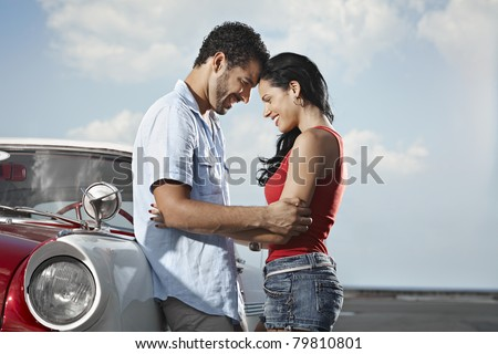 boyfriend and girlfriend leaning on vintage car and hugging in havana, cuba. Horizontal shape, side view, copy space