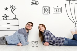 Boyfriend and girlfriend lying on floor of their new apartment, collage with doodle drawings of furniture on white wall