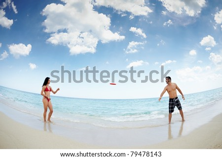 boyfriend and girlfriend playing with frisby on tropical beach. Horizontal shape, full length, fisheye
