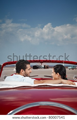 boyfriend and girlfriend sitting in vintage car and hugging in havana, cuba. Vertical shape, rear view, copy space