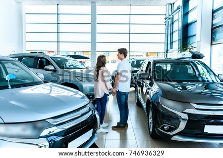 Boyfriend and girlfriend standing face to face in a car showroom