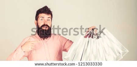 Boyfriend carrying lots of shopping bags and pointing at bags. Man with beard carries bunch of shopping bags, grey background. Recommendation concept. Hipster on surprised face recommends to buy. #1213033330
