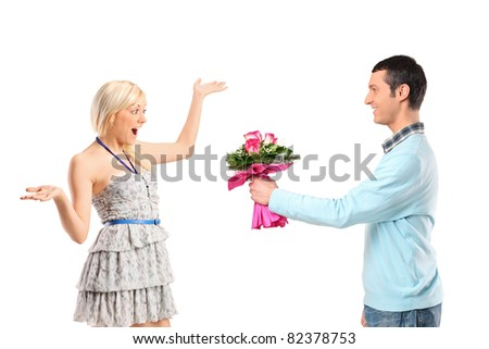 Boyfriend giving flowers to his surprised girlfriend isolated against white background