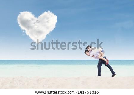 Boyfriend giving piggyback ride under heart cloud on the beach