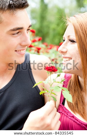 boyfriend giving red flower her girlfriend, smiling young couple