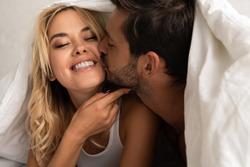 boyfriend kissing girlfriend under sleeping sheets in the morning