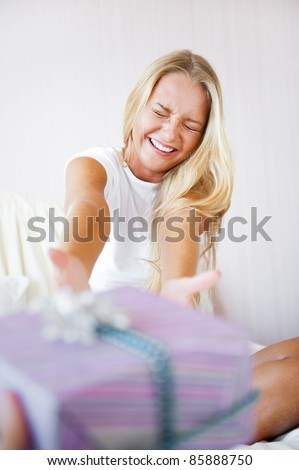 Boyfriend making a gift to his girlfriend in the morning. She is sitting on bed and taking gift box. Smiling laughing and very happy