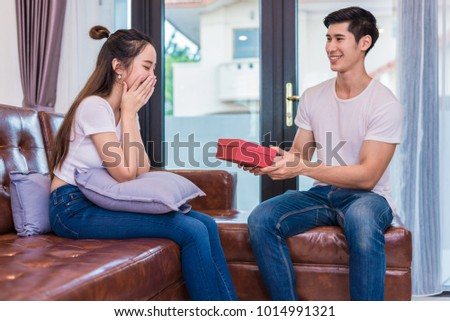 Boyfriend surprising girlfriend with present. Woman surprised when looking at gift box on special day. Lovers and Couples concept. Honeymoon and Dating theme. Happiness and Valentines day theme. #1014991321