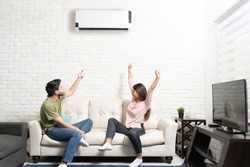 Boyfriend turning on air conditioner while cheerful girlfriend sitting with arms raised on sofa at home