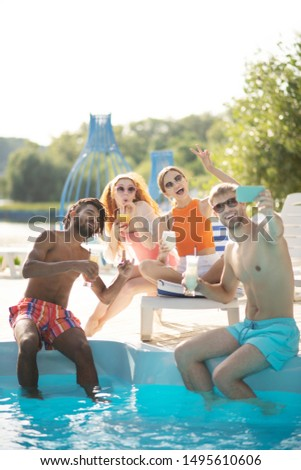 Boyfriends and girlfriends. Boyfriends and girlfriends smiling while taking photo together near pool #1495610606