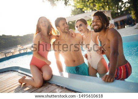 Boyfriends hugging. Strong boyfriends hugging their women while chilling in pool in summer #1495610618
