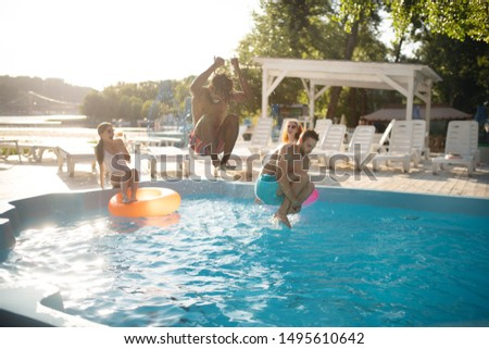 Boyfriends jumping. Boyfriends jumping into water while chilling near pool with women in summer #1495610642