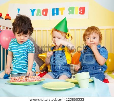 Boys and girl at the birthday party eating cake
