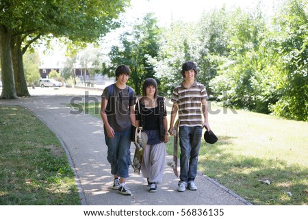Boys and girl with backpacks and skateboards having a walk