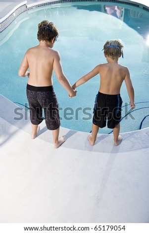 Boys, 7 and 9, looking down at water in swimming pool