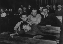 Boys and teenagers attend night school in the Seventh Avenue Lodging House, which was home for a couple hundred 'Street Arabs,' 1900 photograph by Jacob Riis.