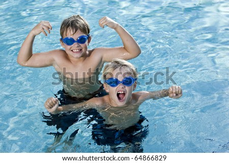 Boys, 7 and 9 years, smiling and shouting in swimming pool
