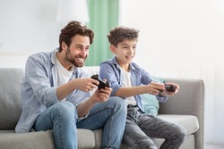 Boys are boys. Joyful father and teen son competing with each other in online video games, using joysticks, having fun at home while sitting on sofa and enjoying time together