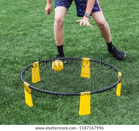 Photo of  Boys are playing spike ball on a green turf field