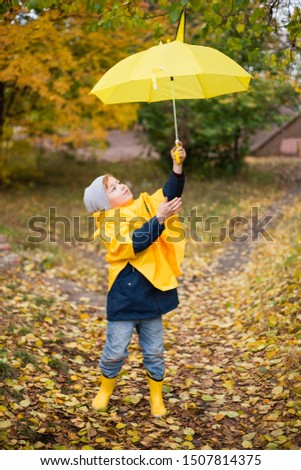 Boys are walking in the autumn park. Autumn style. Children in a raincoat, rubber boots, with an umbrella. walk under the rain. Damp weather