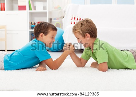 Boys arm wrestling in the kids room - childhood rivalry