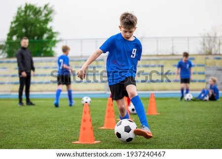 Boys attending soccer training on school field. Young man coaching children on physical education class. Soccer practice for children