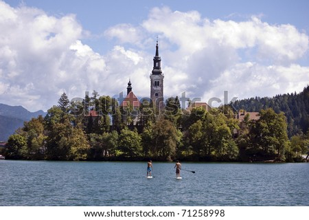 Boys enjoy summer activities on the lake with the church on island, Bled, Slovenia, Europe