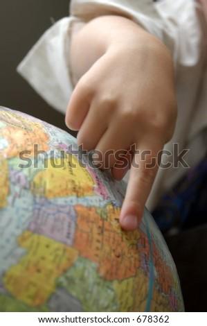 boys finger pointing on world globe