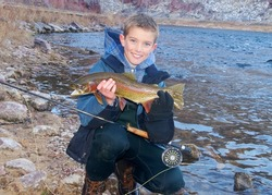 Boys fly fishing - handsome young man next to a river holding a large Rainbow Trout he caught fly fishing