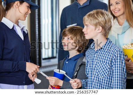 Boys giving movie tickets to female worker at cinema while parents standing in background